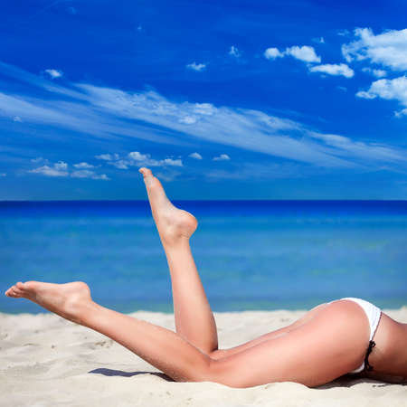 Beautifully tanned legs on the beach Reklamní fotografie