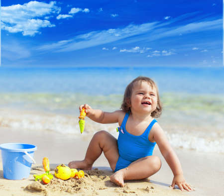 Happy smiling little child girl playing on a sea beach