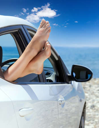 Young woman bare feet sticking out of white car window Foto de archivo