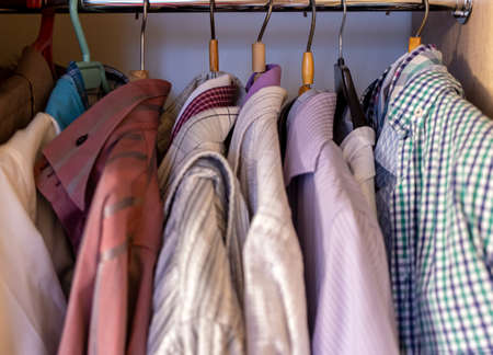 Colorful clothes for man hanging in wardrobe Foto de archivo