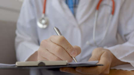 Closeup of male medical doctor making a prescription in medical clinic.