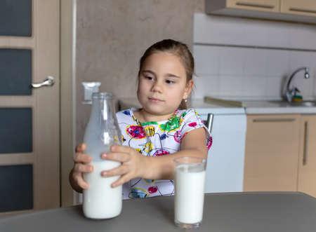 Cute little child girl is drinking milk
