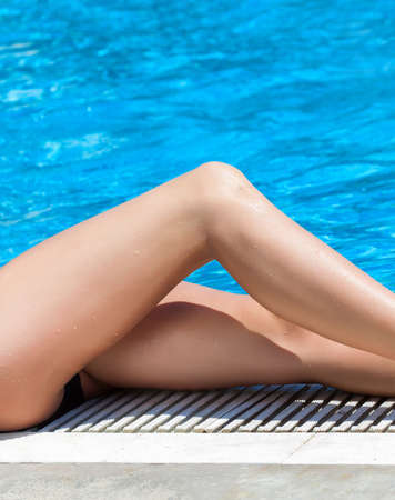 Close-up of female legs is lying on the swimming pool