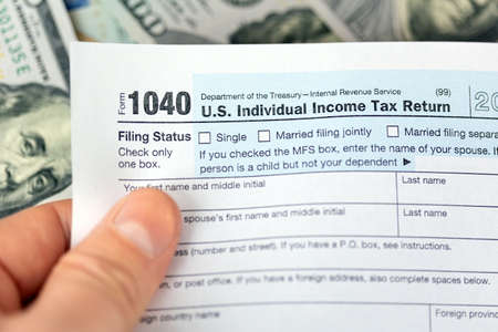 Man hand holding US individual income 1040 tax form 免版税图像