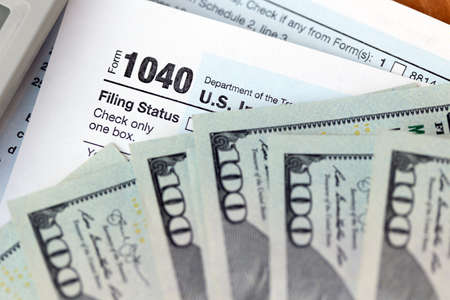 US individual 1040 tax form, calculator and one hundred dollar bills