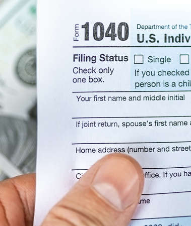 Man hand holding US individual income 1040 tax form 免版税图像 - 164859409