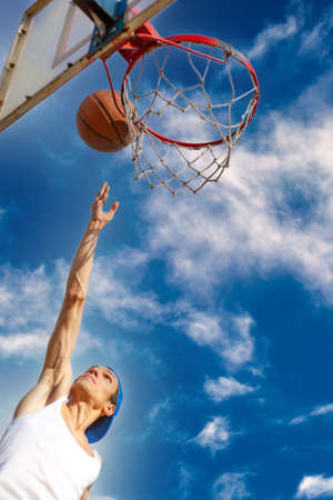 Young guy playing basketball. He is preparing to throw the ball in the basket 免版税图像 - 164859410