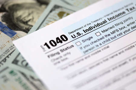One hundred dollar bills and US 1040 tax form.