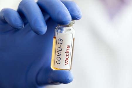 Medical doctor or laboratory holding tube with COVID-19 Coronavirus vaccine 免版税图像