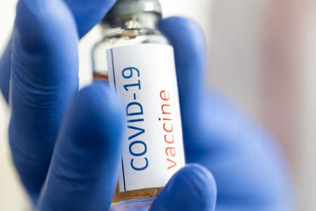 Medical doctor or laborant holding tube with COVID-19 Coronavirus vaccine 免版税图像
