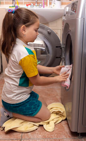 Pretty little child girl putting the towels into the washing machine 免版税图像 - 164714380