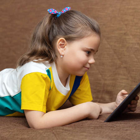 Cute child girl playing with tablet computer on the sofa at the home 免版税图像