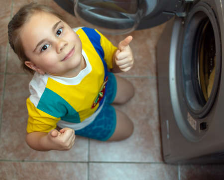 Pretty little child girl putting the towels into the washing machine