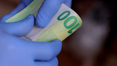 Hands with blue protective medical gloves are counting 100 EURO money banknotes 免版税图像