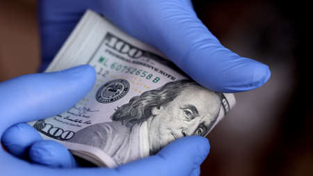Hands with blue medical gloves are counting 100 dollar money banknotes 免版税图像 - 164990832