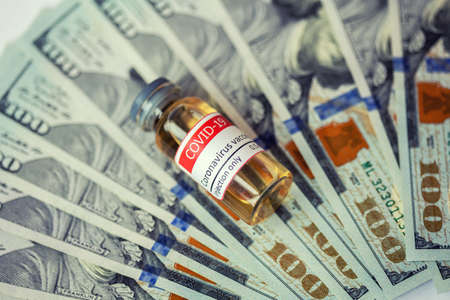 Dollars bills and vial dose of COVID-19 vaccine against dollar bills. 免版税图像 - 165103630
