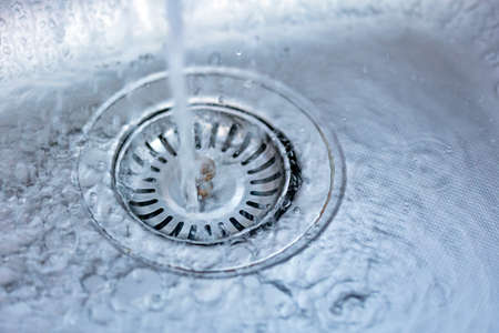 A stream of clean water flowing into the stainless steel sink.