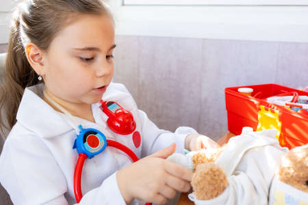 Child girl wearing in white medical uniform playing with teddy bear 免版税图像 - 165422272