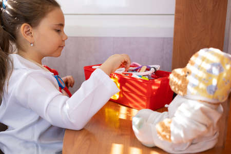 Child girl wearing in white medical uniform playing with teddy bear 免版税图像