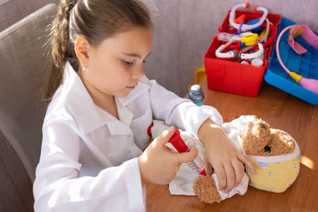 Child girl wearing in white medical uniform playing with teddy bear 免版税图像 - 165890578