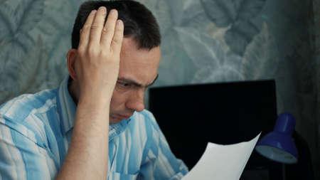 Frustrated man sitting at desk with paper bills. Bankruptcy concept Banco de Imagens