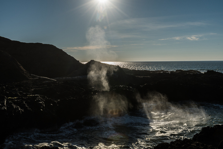 Backlight of the water expelled by a hole in the rock when the waves break in the Spouting Horn Stock Photo