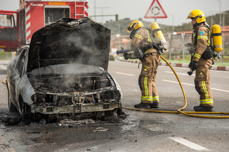 CACERES, EXTREMADURA, SPAIN - APRIL  24, 2018: Firefighters put out a car that has burned on a street in Caceres.