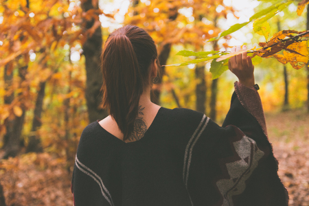A young woman with reddish hair touches the branch of a tree in an autumnal forest
