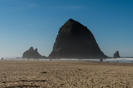 Tourists and locals enjoying the beach with Haystack Rock in the background at Cannon beach, Oregon, USA. Sajtókép