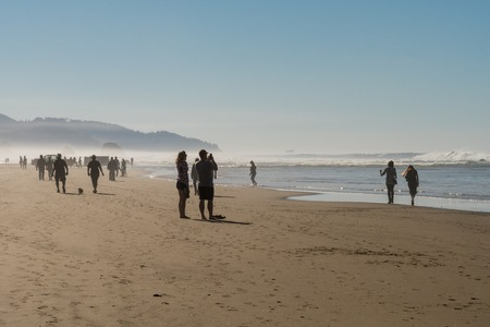 Tourists and locals enjoying the sun at Cannon beach, Oregon, USA.