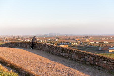 An older man contemplates the sunset over the village in Medellin, Extremadura, Spain. Editorial