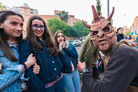 People masquerading as demons frightening people on the occasion of the feast of St. George. Редакционное