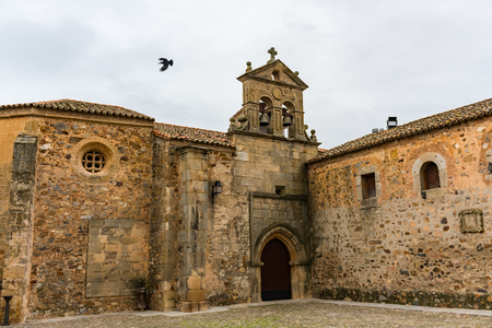 A crow flies over the door of the convent of San Pablo in the old town of Cacere.