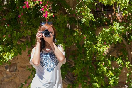A young woman with reddish hair takes photographs with her camera next to a wall covered with bougainvillea Caceres