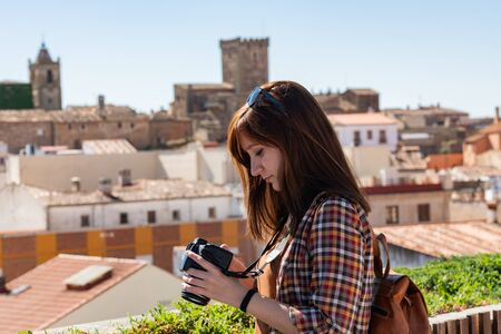 A young red-haired tourist with a backpack takes photographs of the old town of Caceres from the viewpoint of Galarza