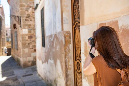 Young red-haired tourist takes photographs with her camera of the narrow streets of the old town of Caceres