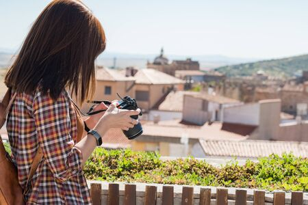 A young red-haired tourist takes photographs of the old town of Caceres from the viewpoint of Galarza