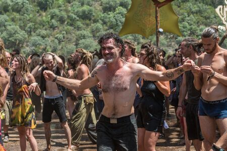 Man with naked torso dances uninhibited of the Lost Theory psytransce music festival held in Riomalo de Abajo Archivio Fotografico - 133365063