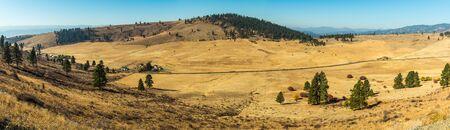 Paysage de la plaine de Hidden Valley avec un sol jaunâtre et quelques arbres et ranchs à Cle Elum