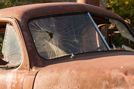 Detail of the broken front glass of an old rusty and abandoned pickup in Maryhill