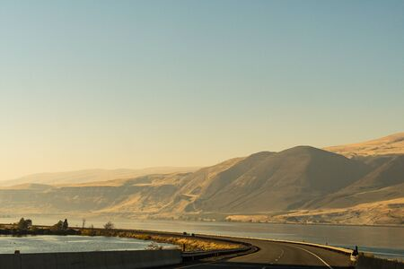 The US-30 highway passing by the Columbia River with water on both sides of the road near The Dalles