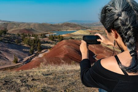 A young woman with dark hair and gray hair makes a photograph with her smartphone from the Painted Hill Reservoir, Oregon, USA Banque d'images