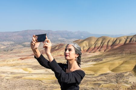 A young brunette with gray strands takes selfies at Painted Hills Overlook