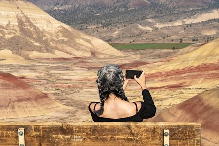 A young brunette with gray strands takes photographs with her smartphone sitting on a bench in Painted Hills Overlook, Oregon, USA.