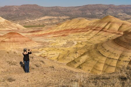 A young brunette with gray hair takes pictures with her smartphone in Painted Hills Overlook, Oregon, USA.