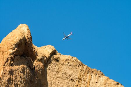 An airplane flies over one of the rock walls of Smith Rock State Park