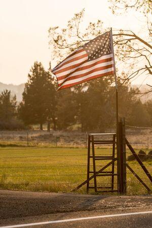 Sunset light passes through a waving U.S. flag near Terrebonne Stock Photo