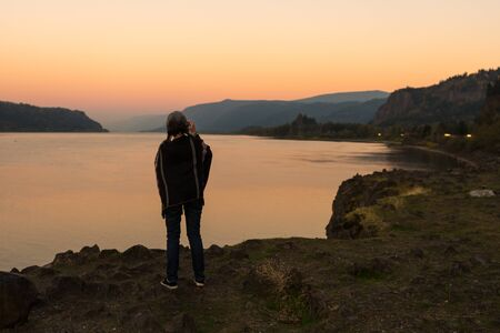 Young woman with poncho takes photographs of the sunset at the Corbett lookout on the Columbia River, Oregon