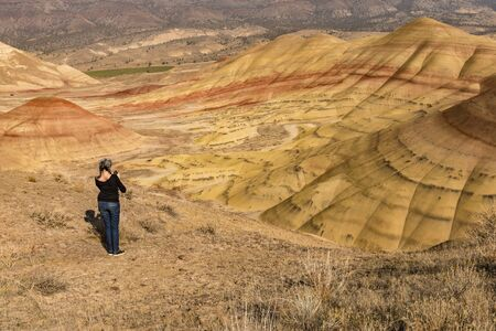 A young brunette with gray hair takes pictures with her smartphone in Painted Hills Overlook