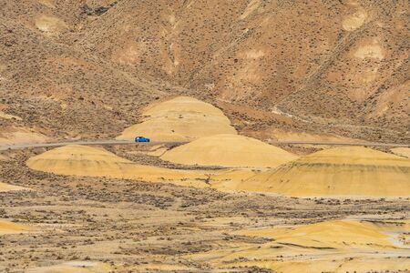 Cars in the distance crossing the deserted, wavy and colorful landscape of Painted Hills